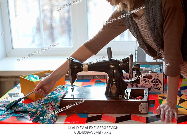 Woman with vintage sewing machine reaching for scissors at table