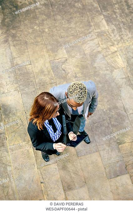 Young businessman and woman looking at digital tablet