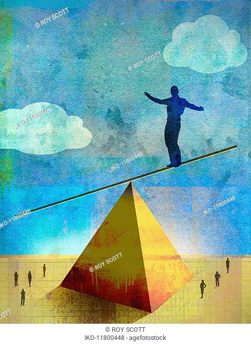 Businessman precariously balancing on top of pyramid