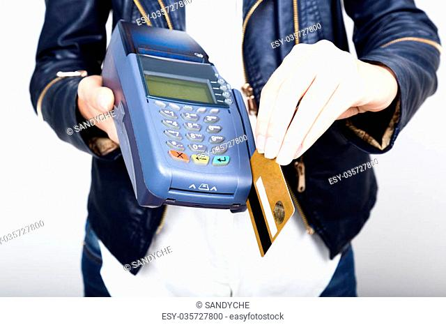 Payment card in a bank terminal. The concept of of electronic payment. Closeup of a woman hand holding credit card over payment terminal