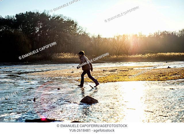 Child walks along the beach in winter beach, Ispra, Lake Maggiore, Italy
