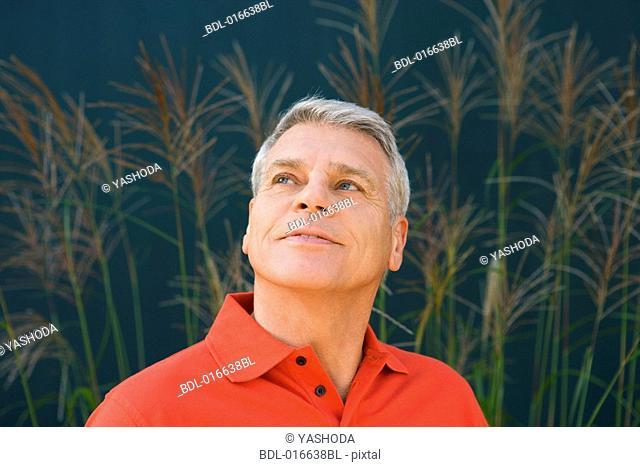 headshot of mature man wearing red shirt