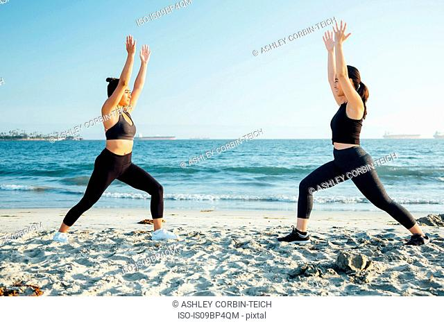 Friends doing exercises on beach, Long Beach, California, US