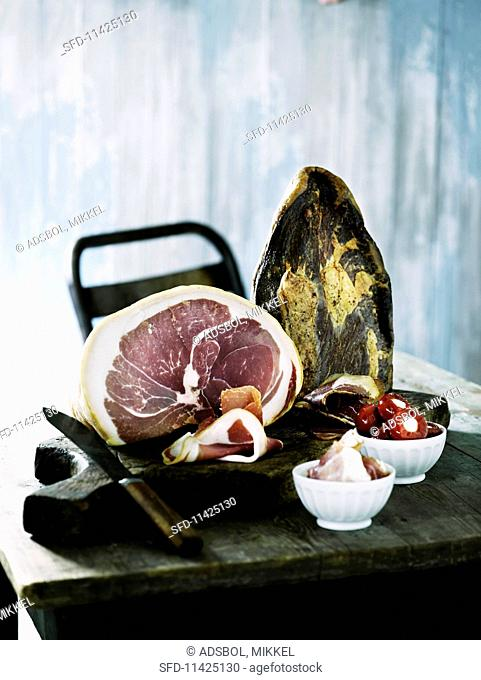 Sliced raw ham and stuffed peppers on a rustic wooden table
