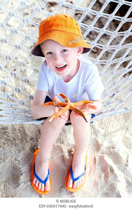 little boy holding starfish at the beach