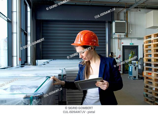 Woman in warehouse wearing hard hat looking holding digital tablet checking stock