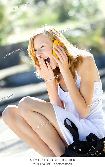 Laughing young woman uses cellphone