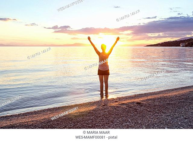 Greece, Pelion, Pagasetic Gulf, woman on the beach with raised arms at sunset, Kalamos in the background