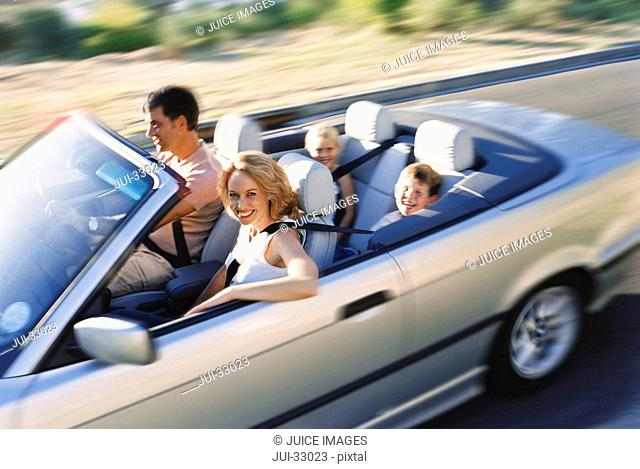 Smiling family riding in convertible together