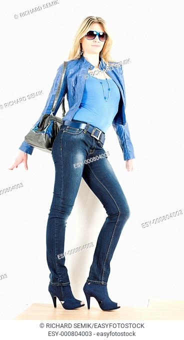 standing woman wearing blue clothes with handbag