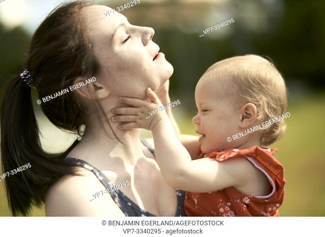 young mother feeling hands of baby toddler daughter on her throat