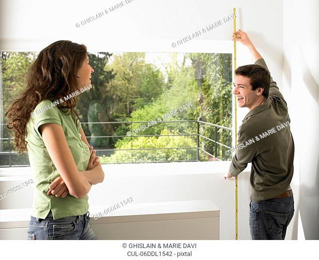 Couple taking measurement of their home