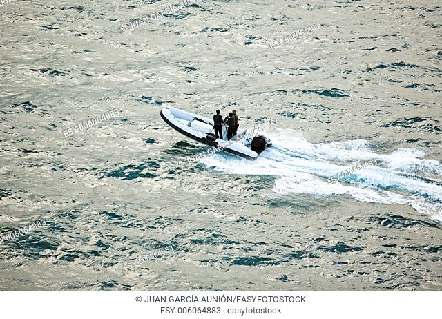 Three men on infatable motorboat crossing the cape, Sagres, Portugal