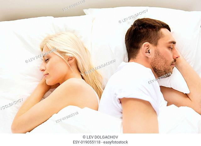 people, rest, bedtime and family concept - couple sleeping back to back in bed at home