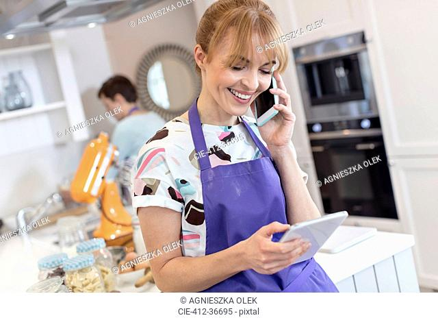 Smiling caterer working, talking on cell phone and using digital tablet in kitchen