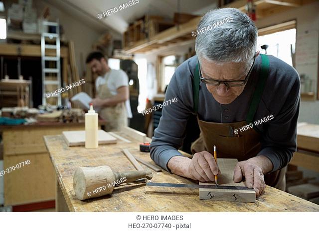 Carpenter measuring and marking wood piece in workshop