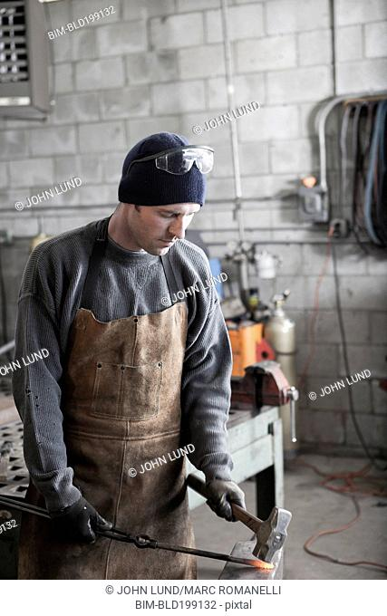 Caucasian metal worker pounding metal in workshop
