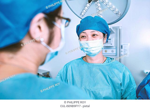 Over shoulder view of surgical team wearing scrubs having discussion in maternity ward operating theatre