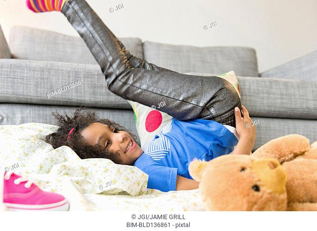 African American girl playing on living room floor