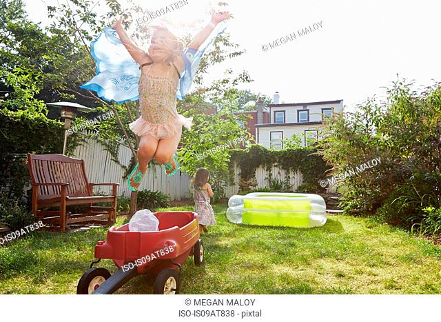 Girl in butterfly costume jumping up from toy wagon