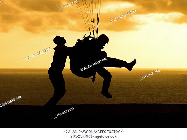 Paraglider taking off at sunset at Los Coloradas at sunset. Las Palmas, Gran Canaria, Canary Islands, Spain