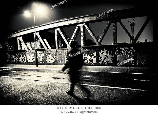 Silhouette of unrecognizable man walking on bridge by night. Street light. Regent's Park Rd. London, England