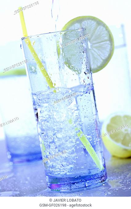 Serving water in blue glass with water, lemons slices and yellow straws