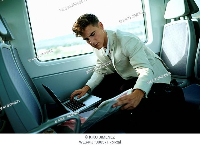 Young man using a laptop on a train
