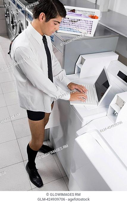 Businessman working on a laptop in a laundromat
