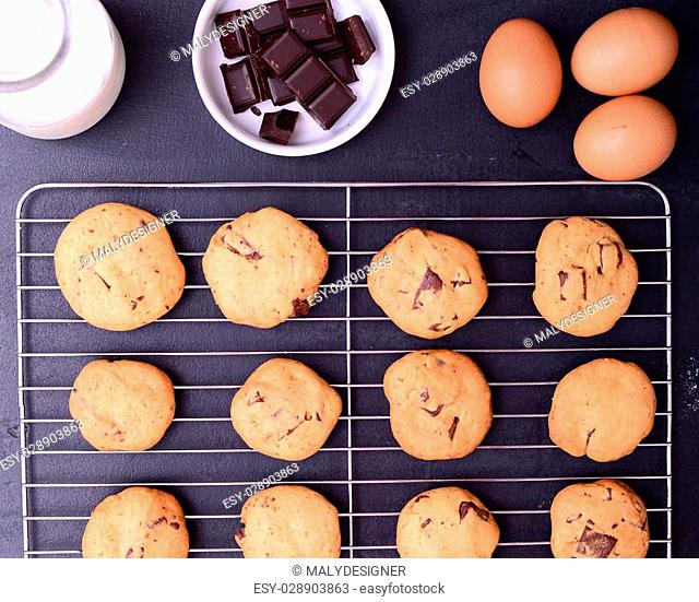 Home baked chocolate cookies on cooling rack with ingredients on black background