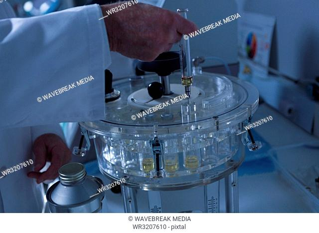 Male scientist pouring solution in medical vials