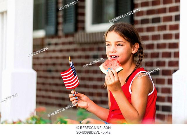Young girl outdoors, holding small American flag, eating slice of watermelon
