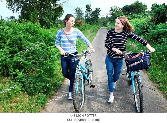 Two young adults pushing bicycles and chatting along country lane