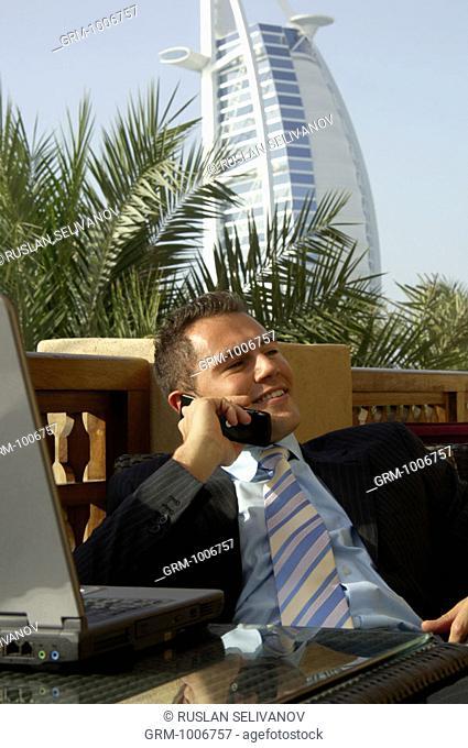 Businessman using mobile phone and laptop in Dubai (Burj Al Arab Hotel in background)