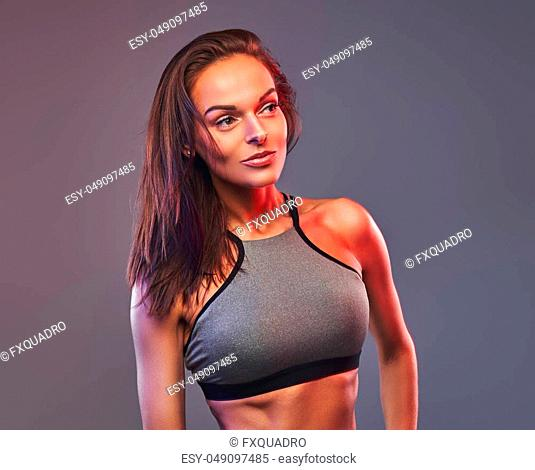 Slim fitness brunette woman in a gray sportswear posing in a studio. Isolated on a gray background