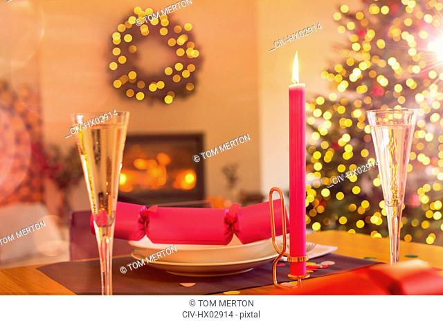 Champagne flute, candle and Christmas cracker on ambient table