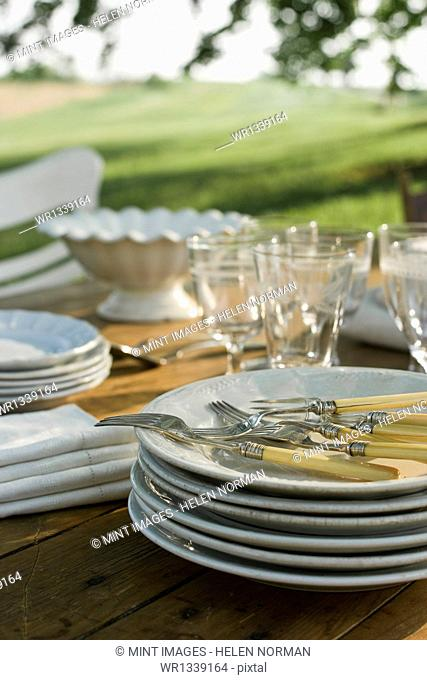 A table laid in a garden, with white china crockery and cutlery. Summer