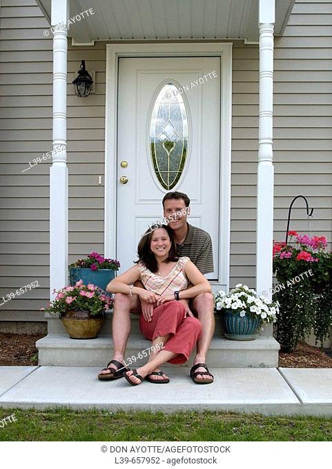 Couple sitting outside a condo in South Hadley, MA, USA