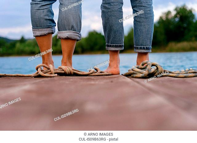 Two women, standing on pier, barefoot, low section, rear view