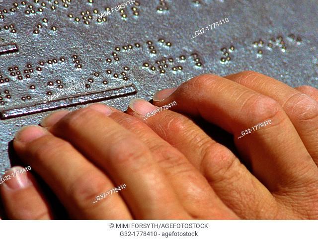 man reading Braille plaque