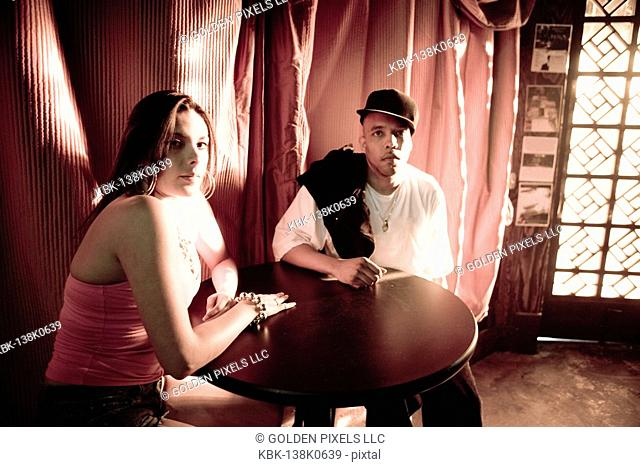 Young couple in hip-hop fashion sitting at a table