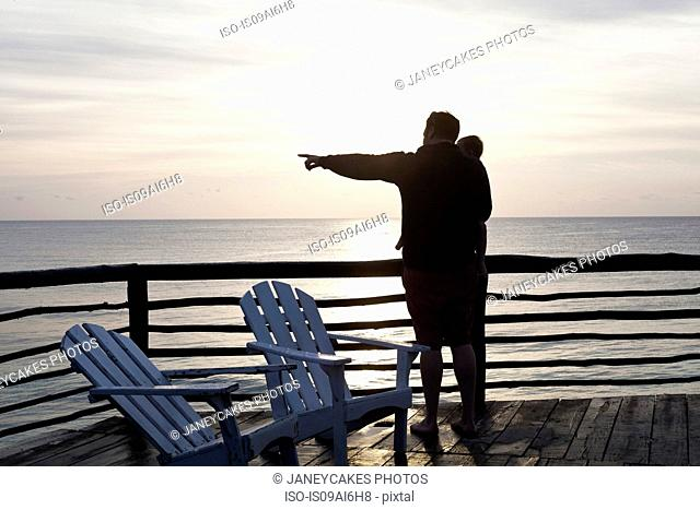 Father holding daughter and pointing out to sea in Tulum, Mexico