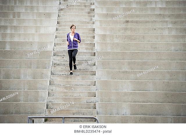 Caucasian woman running on stadium staircase