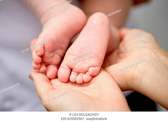 family, motherhood, parenting, people and child care concept - close up of newborn baby feet in mother hands