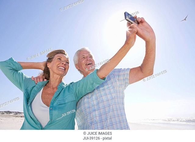 Senior couple with digital camera taking self-portrait on sunny beach