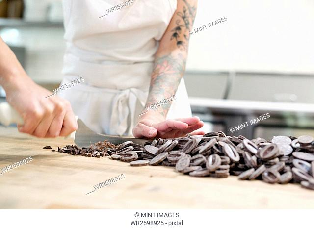 Close up of a woman wearing a white apron standing at a work counter in a bakery, chopping chocolate
