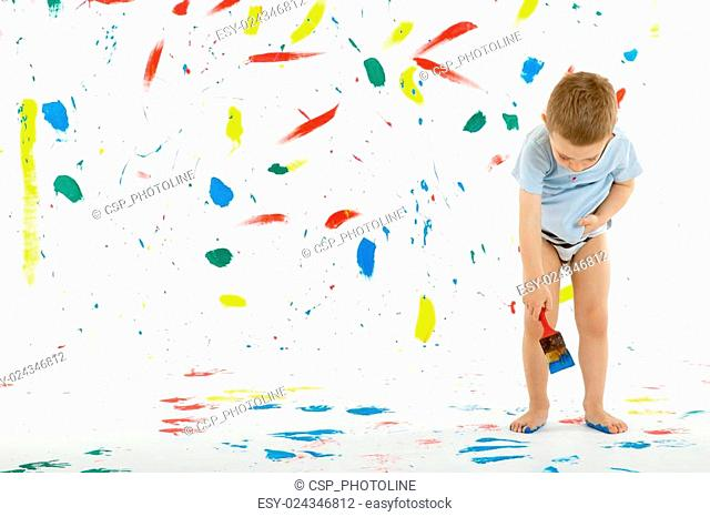 Adorable 3 year old boy child creatively stains on the wall