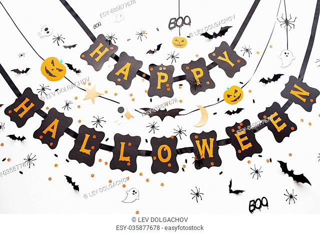holidays, decoration and party concept - happy halloween festive paper black garland or banner with bats and spiders over white background