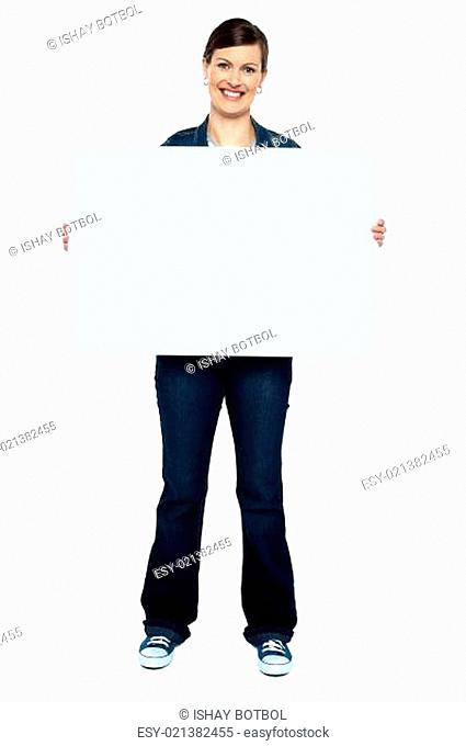 Fashionable trendy woman holding blank ad board