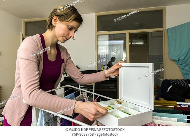 Tilburg, Netherlands. Young, caucasian woman nesting in her newly aquired apartment, figuring out how to deal with her new place to live